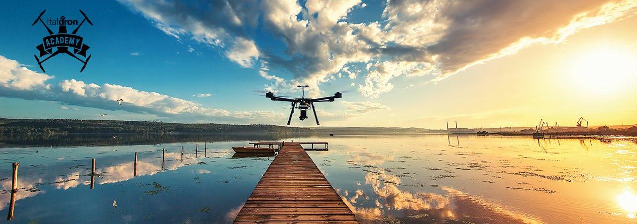 Drone al tramonto sul mare con logo di Italdrone Academy, scuola certificata ENAC
